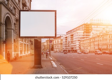 Horizontal blank billboard on the city street. In the background buildings and road with cars. Film effect. Mock up. The poster on the street next to the roadway.