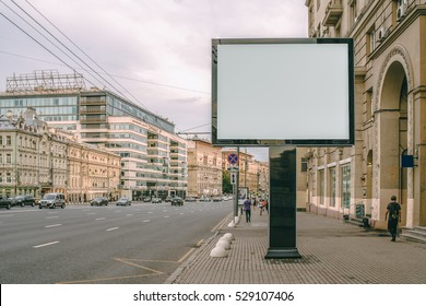 Horizontal blank billboard on the city street. In background buildings and road with cars. Mock up. The poster on the street next to the roadway.