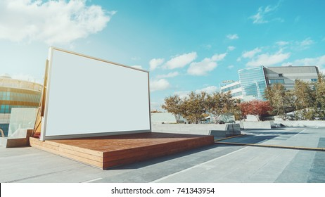 Horizontal blank information banner standing near wooden stage, empty mock-up of poster in urban settings, white clean billboard with copy space for logo, text or other advertising on bright day