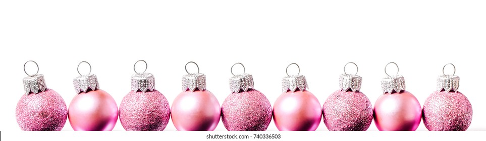 Horizontal border of   pink  Christmas balls on wite background. Flat lay, top view