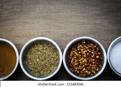 A horizontal border of spices in stainless steel prep bowls over a wooden background with copy space above.