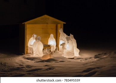 horizontal Christmas image of baby Jesus and the shepherds in a nativity scene at night time.