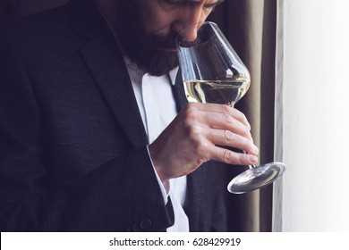 horizontal close up of a Caucasian man with beard black suit and white shirt tasting a glass of white wine by the window natural lighting