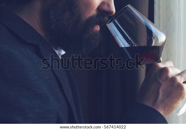 horizontal close up of a Caucasian man with beard, black suit and white shirt tasting a glass of red wine in front of a window