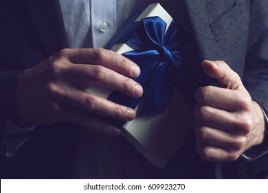 Horizontal close up of Caucasian man in black suit and white shirt taking out a large gift box with blue ribbon from his jacket inner pocket