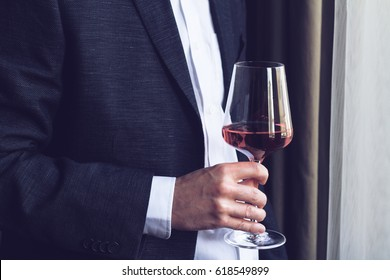 Horizontal close up of Caucasian man in black suit and white shirt holding a tall glass with rose wine  at an event by the window natural lighting
