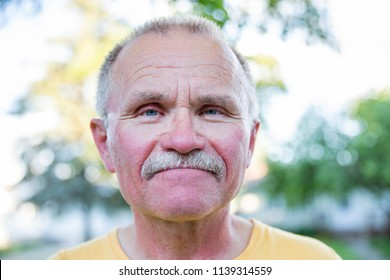 horizontal close up head shot of a middle aged caucasian man with sun burn on his face with copy space.