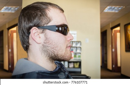 horizontal close up head shot of a profile of a caucasian man sitting in a doctors office wearing dark sunglasses right after laser eye surgery.