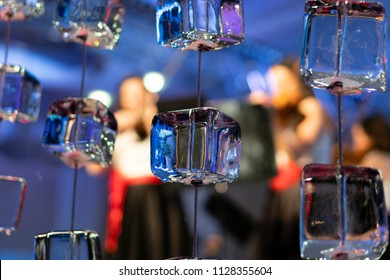 Horizontal close up of ice cubes on strings with a blurry background of  musicians .