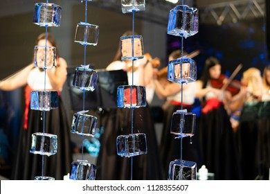 Horizontal close up of ice cubes on strings with a blurry background of musicians in dresses playing the violin.