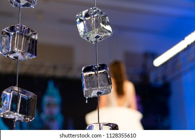 Horizontal close up of ice cubes on strings with a blurry blue background with a girl in a white dress in the right corner.