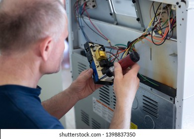 horizontal close up image  of a caucasian  adult male fixing the panel attaching wires at the back of an electric stove.