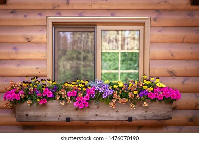 horizontal close up image of a log cabin with a window and window box full of colorful vibrant flowers in the summer time.