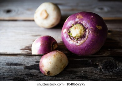 horizontal  close up image of three raw wet rutabaga lying on a rustic wood background with copy space