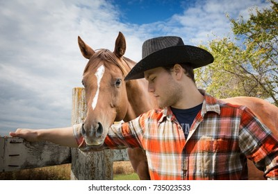 horizontal close up image of a young caucasian cowboy wearing a checkered shirt and black cowboy hat with his brown horses standing close beside him.