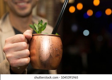 Horizontal close up of a man  holding a moscow mule cocktail, served in a copper mug , with focus on the drink.