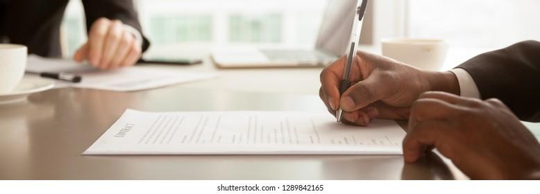 Horizontaler Nahaufnahme-Fotoafrikanischer Geschäftsmann, der am Schreibtisch sitzt, verfügt über Schreibstift-Unterzeichnungspapier, Leasinghypotheken, Beschäftigungsbzw. Partnervermittlungskonzept, Banner für Website-Header-Design