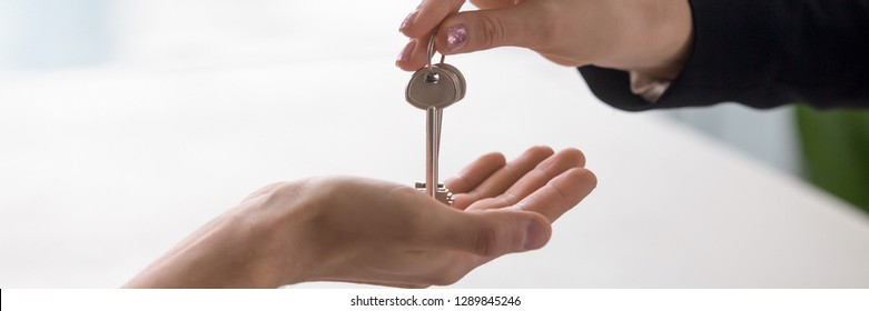 Horizontal close up photo with copy space for text real estate agent hand giving keys from property to owner, buying selling home, loan mortgage, renting tenancy concept banner website header design