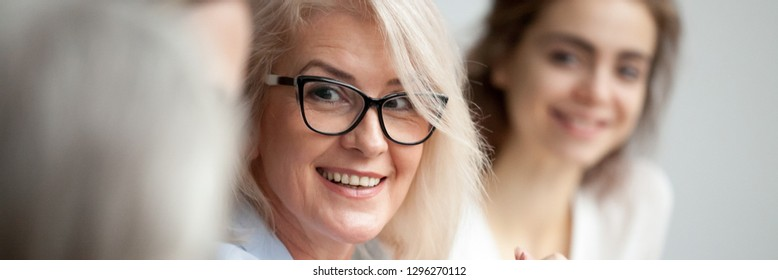 Horizontal close up photo focus aged attractive businesswoman boss in glasses listen colleague ideas information at briefing meeting negotiation with business partners banner for website header design