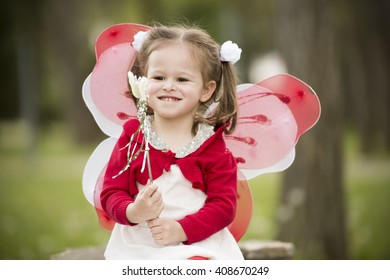 horizontal close up portrait of a little girl sitting on a park bench in spring, smiling, wearing a white dress, red blouse, with butterfly wings on her back and holding a magic wand in her hands