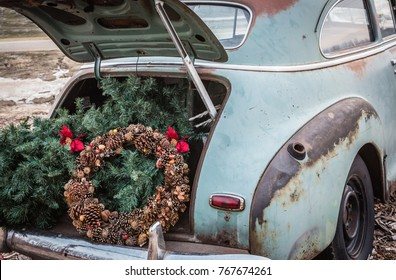 horizontal close up rustic image of the back end of an old green vintage car with the trunk open and a brown acorn Christmas wreath and Christmas tree in the back of trunk.