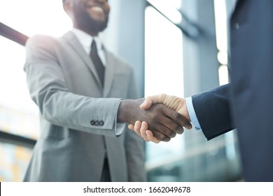 Horizontal close up shot of two unrecognizable businessmen standing in front of each doing handshake