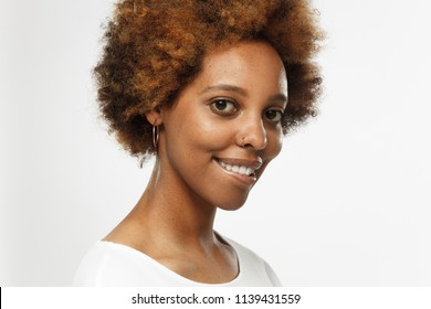 Horizontal closeup headshot of young smiling flirty dark skin african american woman  isolated on gray background, having turned head and biting her lips
