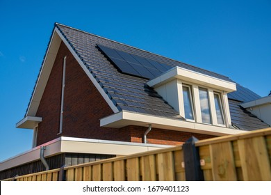 Horizontal close-up image of modern urban home dark roofing, white dormer and solar panels. Black tiled roof with dormer in the Netherlands. Photovoltaic installation rooftop, alternative electricity.