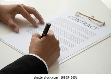 Horizontal close-up photo Asian businessman sitting at his desk holding paper, signing contract, mortgage pen, lease contract, employment hour or confirming concept, partnership agreement, banner for