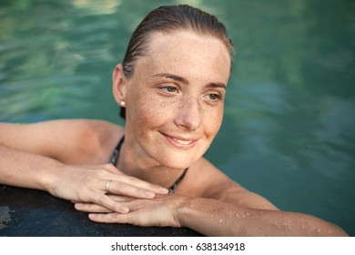 Horizontal close-up portrait of beautiful girl with sunspots and wet hair in water, arms on pool edge