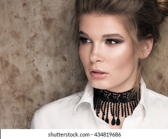 Horizontal closeup portrait of a beautiful young woman in a white shirt with a black choker on her neck. Professional Nude-makeup. Perfect clean skin. Hair in a bun. Metal wall in the background