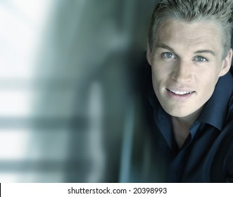 Horizontal close-up portrait of a smiling confident young male model with a futuristic modern background with lots of copy space