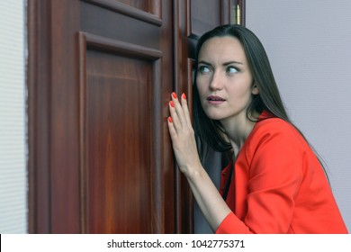 Horizontal close-up portrait of a woman in a red suit eavesdropping, spying on the door of the boss.