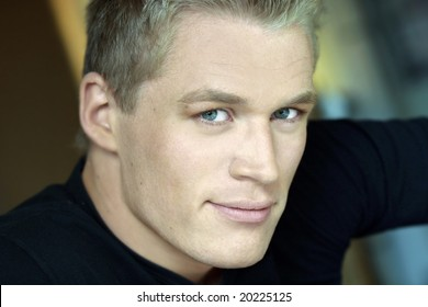 Horizontal close-up portrait of young male model with blond hair and green eyes