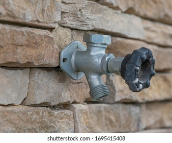 Horizontal close-up shot of an outdoor water faucet attached to a stone wall. The background is partially blurred.
