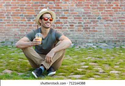 Horizontal closeup of young Caucasian man pictured on left side sitting on grass and stones with red brick background behind drinking fresh juice from plastic cup and watching street with interest