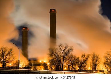 horizontal color image of coal fueled power plant with visible smoke stacks and columns of steam