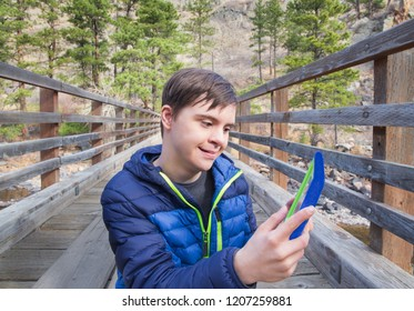 horizontal color image of a happy teenage boy with autism and down's syndrome outside using his tablet