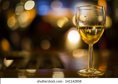 horizontal color image of wine glass and lights