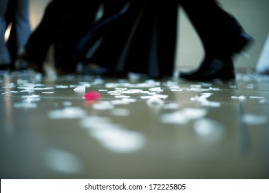 Horizontal colour image of people dancing with floor covered in confetti