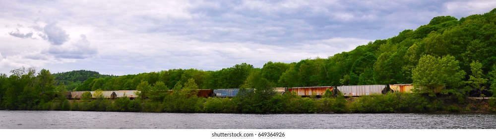 Horizontal composition of an old freight train chugging along the country side by a river. Great for a banner or heading.