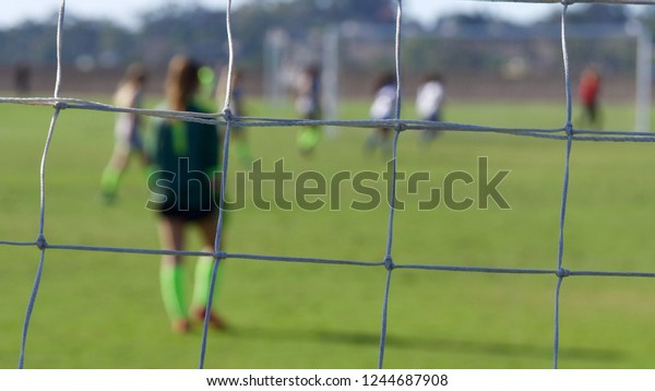 Horizontal composition of a soccer goalie through goal net in focus with shallow depth of field players in background.