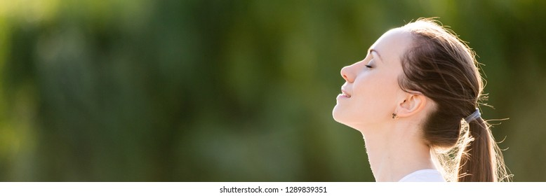 Horizontal conceptual photo profile portrait relaxed woman face closed eyes breath fresh clean air outdoors enjoying nature weather feels good banner for website header design with copy space for text