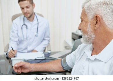 Horizontal crop closeup view of doctor and patient during medical examination. Young doctor providing consultation for senior man in hospital. Elderler man sitting and taking blood pressure.