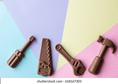 horizontal Easter image of chocolate hand tools spread over a background of purple and yellow blue and pink with room for text.
