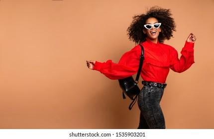 Horizontales Modebild aufgeregter schwarzer Frauen, die mit fröhlichem Gesichtsausdruck auf beigem Hintergrund springen. Vintage-Rot-Hemd tragen