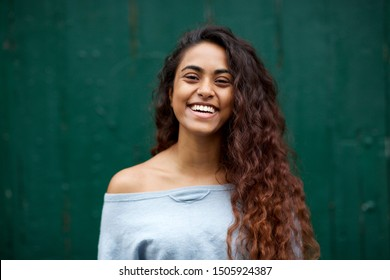 Horizontal front portrait of happy young Indian woman laughing against green background