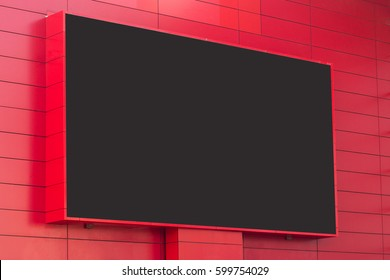 horizontal front view of outdoor digital display with blank screen on red building exterior wall