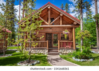 horizontal  frontal image of a new modern log cabin sitting in the woods on a sunny summer day.