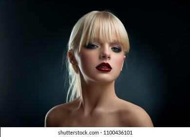 Horizontal frontview of model wearing evening make up. Girl having big blue eyes, short blonde hair and pretty face with plump lips, covered with dark red lipstick. Posing with opened shoulders.